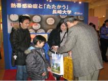 青木教授から記念品を渡 される1 万人目の入場者