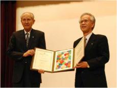 授与された名誉博士記を披露する 下村名誉博士(左)と片峰学長