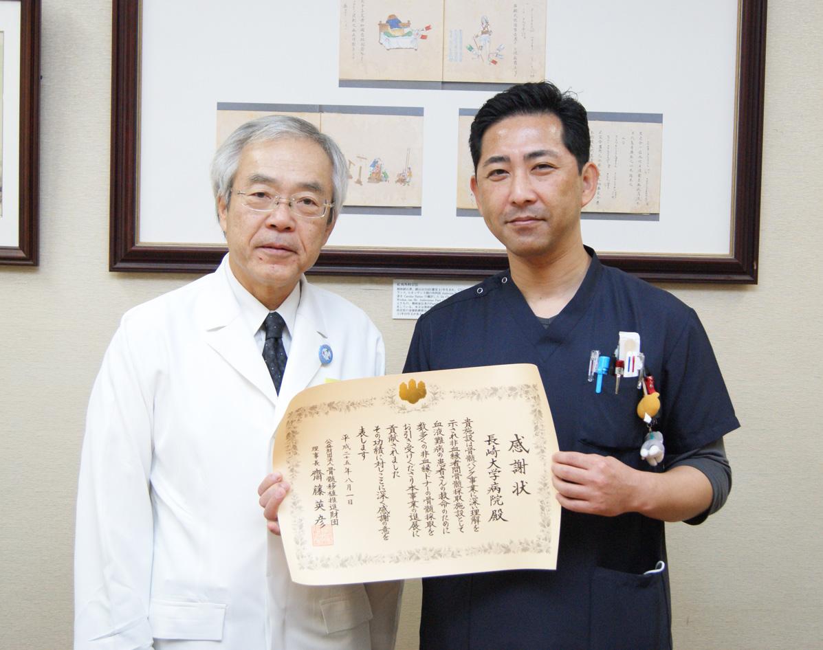 河野病院長と記念撮影する田口助教