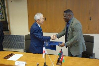 協定書を交換し、握手する河野学長 とKombe所長