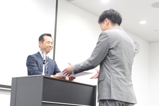 賞状を授与する永安医学部長と受賞者の古賀助教