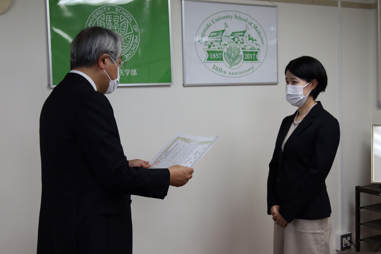 医学部長から表彰状を授与される折田助教